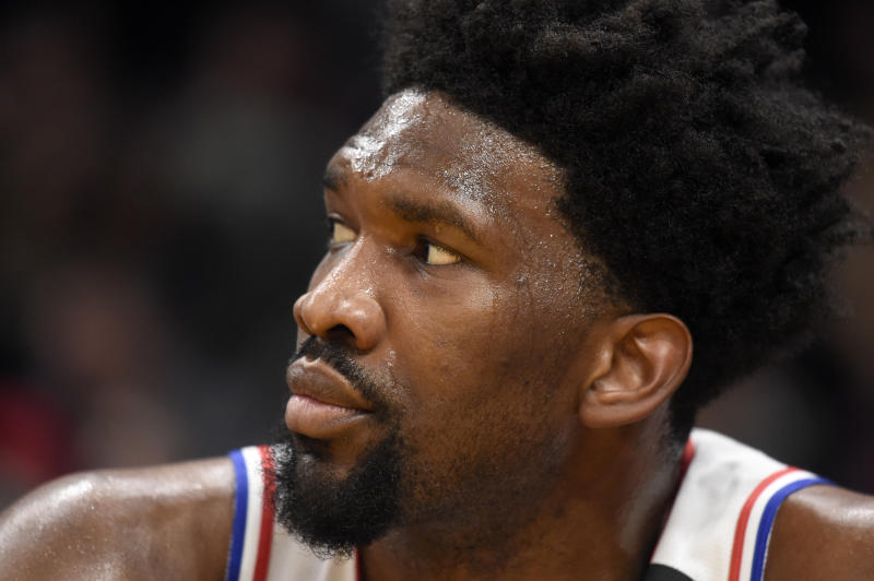 Joel Embiid watches from 76ers bench.