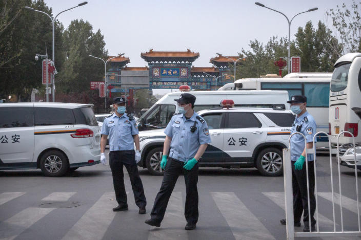 Chinese police stand guard outside an entrance to the Xinfadi wholesale food market district in Beijing, Saturday, June 13, 2020. Beijing closed the city's largest wholesale food market Saturday after the discovery of seven cases of the new coronavirus in the previous two days. (AP Photo/Mark Schiefelbein)