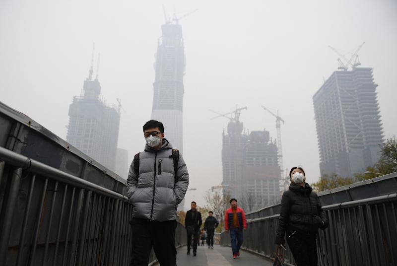 People wear masks on a polluted day in Beijing on November 18, 2016