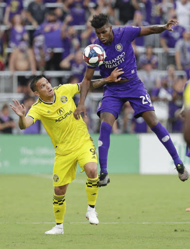 Columbus Crew's David Guzman (9) and Orlando City's Carlos Ascues (26) battle for possession of the ball during the first half of an MLS soccer match Saturday, July 13, 2019, in Orlando, Fla. (AP Photo/John Raoux)