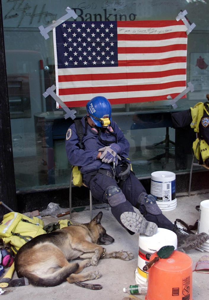 A canine officer and his dog take a much needed rest September 18, 2001 after search duty at the World Trade Center site. (REUTERS/Pool/Ryan Remiorz)