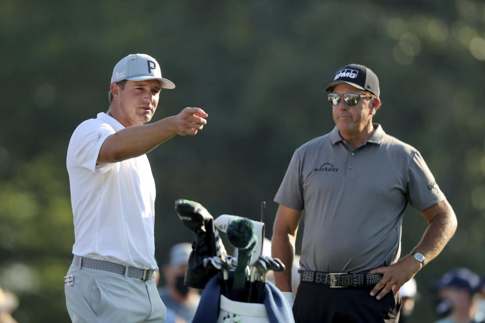 Bryson DeChambeau, left, talks with Phil Mickelson on the 10th tee during a practice round for the Masters golf tournament in Augusta, Ga., Wednesday, April 7, 2021. (Curtis Compton/Atlanta Journal-Constitution via AP)