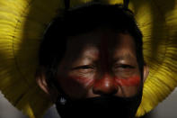 An Indigenous man wearing a mask amid the COVID-19 pandemic takes part in a protest against Brazilian President Jair Bolsonaro's proposals to allow mining on Indigenous lands, at the entrance of the Chamber of Deputies in Brasilia, Brazil, Wednesday, June 16, 2021. (AP Photo/Eraldo Peres)