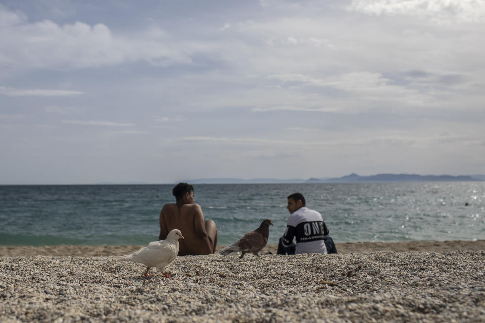 Two men sit at the beach of Alimos, a seaside suburb of Athens, on Friday April 23, 2021. Easter holidays are often celebrated with relatives outside Athens and other cities, but the government has said COVID-19 infection levels remain too high to allow free travel.(AP Photo/Petros Giannakouris)