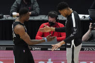 Milwaukee Bucks players Thanasis Antetokounmpo, left, and Giannis Antetokounmpo, right, give five before an NBA basketball game against the Chicago Bulls in Chicago, Sunday, May 16, 2021. (AP Photo/Nam Y. Huh)