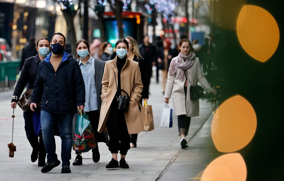 Pedestrians wearing a face mask or covering due to the COVID-19 pandemic, walk along Oxford Street in central London on December 22, 2020. - UK government borrowing continued to soar in November on emergency action to support the virus-hit economy which nevertheless rebounded stronger than expected in the third quarter, official data showed Tuesday. Government borrowing last month hit £31.6 billion ($41.8 billion, 34.2 billion euros), a record for November -- taking public sector net debt to £2.1 trillion, the Office for National Statistics said in a statement. (Photo by Tolga Akmen / AFP) (Photo by TOLGA AKMEN/AFP via Getty Images)