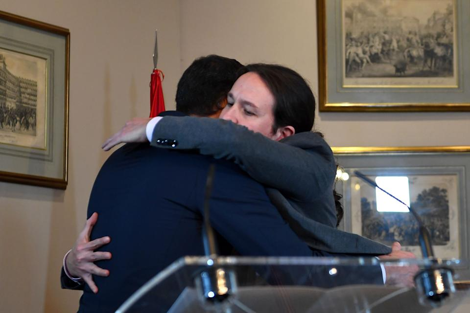 """Spanish incumbent prime minister Pedro Sanchez (L) and the leader of the left-wing electoral alliance """"Unidas Podemos"""" Pablo Iglesias (R) great each other after a press conference in Madrid on November 12, 2019, after announcing an agreement to form a governement two days after a repeat general election. (Photo by GABRIEL BOUYS / AFP) (Photo by GABRIEL BOUYS/AFP via Getty Images)"""