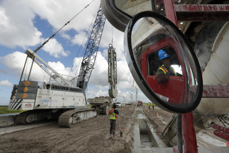 In this Friday, Oct. 25, 2019, photo, workers use heavy equipment to strengthen the 1930s-era Herbert Hoover Dike ringing Lake Okeechobee, at South Bay, Fla. (AP Photo/Robert F. Bukaty)