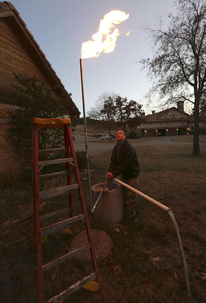 In this Nov. 27, 2012 photo, a well vent burns as water flows from Steve Lipsky's well outside his family's home in rural Parker County near Weatherford, Texas. The U.S. Environmental Protection Agency had evidence a gas company's drilling operation contaminated Lipsky's drinking water with explosive methane, and possibly cancer-causing chemicals, but withdrew its enforcement action, leaving the family with no useable water supply, according to a report obtained by The Associated Press. The EPA's decision to roll back its initial claim that hydraulic fracturing, or ìfracking,î operations had contaminated the water is the latest case in which the federal agency initially linked drilling to water contamination and then softened its position, drawing criticism from Republicans and industry officials who insisted they proved the agency was inefficient and too quick to draw conclusions. (AP Photo/LM Otero)