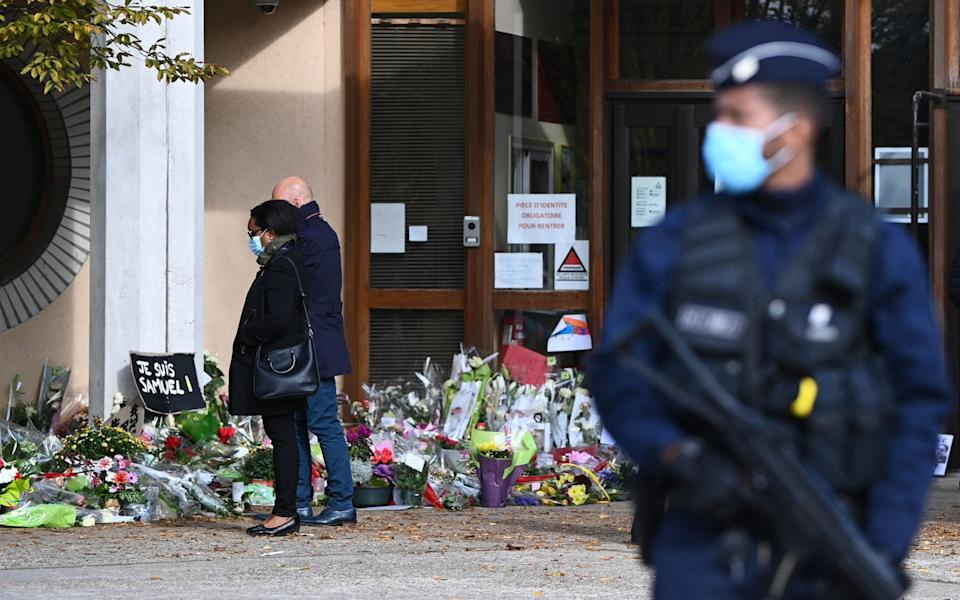 People look at flowers layed outside the Bois d'Aulne secondary school in homage to slain history teacher Samuel Paty - AFP
