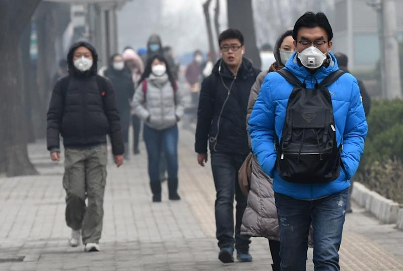 Pedestrians wear protective masks in Beijing on December 8, 2015 as authorities issue a red alert for air pollution (AFP Photo/Goh Chai Hin)