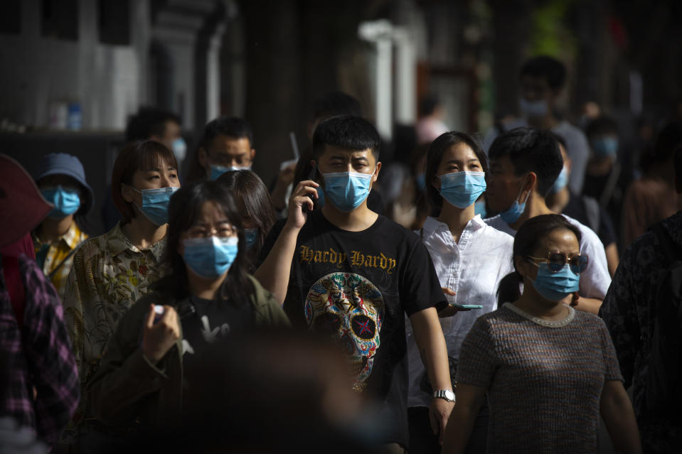 People wearing face masks to protect against the spread of the new coronavirus walk along a pedestrian shopping street in Beijing, Saturday, May 16, 2020. According to official data released on Saturday India's confirmed coronavirus cases have surpassed China's. (AP Photo/Mark Schiefelbein)