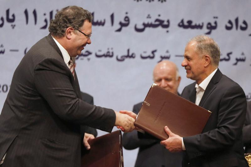 Patrick Pouyanne (L), Chairman and CEO of French energy company Total, shakes hands with Ezzatollah Akbari, managing director of Petropars Group, after signing an offshore gas field agreement in Tehran on July 3, 2017 (AFP Photo/ATTA KENARE)