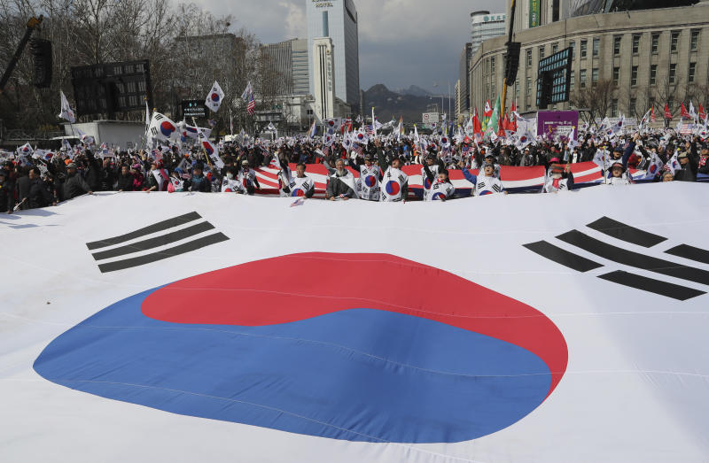 Supporters of former President Park Geun-hye shout slogans as they carry a huge national flag during a rally at downtown Seoul, South Korea, Saturday, April 1, 2017. Supporters of arrested former President Park rallied in South Korea's capital Saturday for her release. (AP Photo/Lee Jin-man)