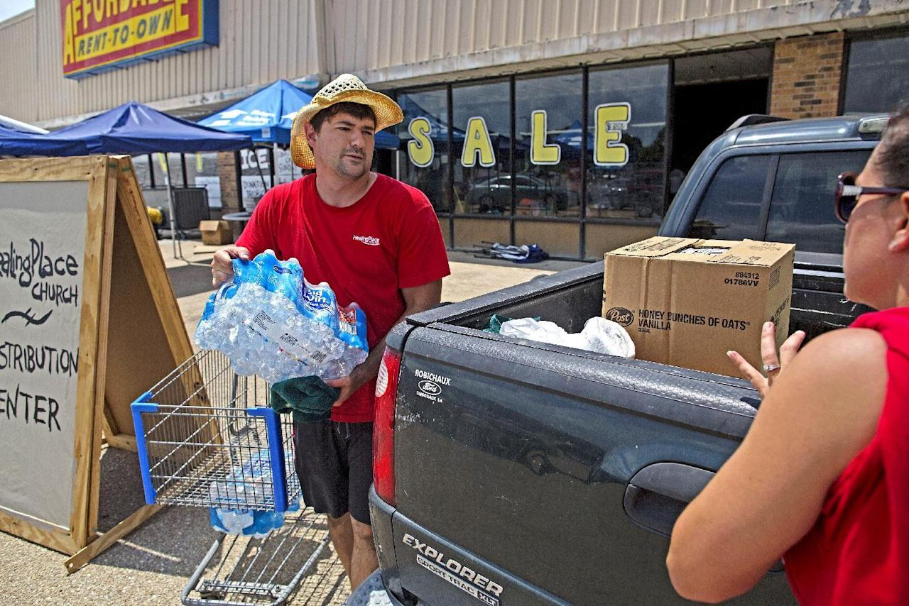 Pastor Michael Campagna, left, helps load bottled water given to flood victims as part of the emergency aid operations of Healing Place Church in Denham Springs, La., Wednesday, Aug. 24, 2016. Volunteers have served thousands of free meals and passed out carloads of clothes, food, cleaning supplies and other essentials. (AP Photo/Max Becherer)
