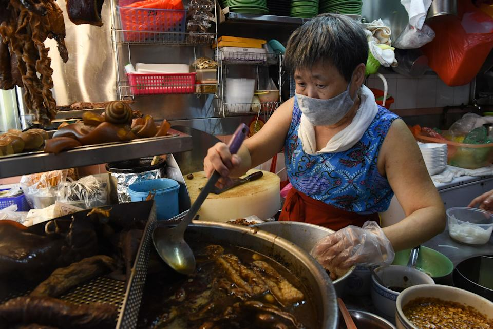 This photo taken on April 21, 2020 shows Lim Bee Hong ladling a broth of spices and herbs as she prepares food at her small food stall, as the business has moved to delivery only due to the COVID-19 coronavirus outbreak in Singapore. - From Facebook groups to hyper-local delivery services, Southeast Asia's street food chefs are cooking up creative ways to sell their wares as they struggle to survive amid the coronavirus pandemic. (Photo by Catherine LAI / AFP) (Photo by CATHERINE LAI/AFP via Getty Images)