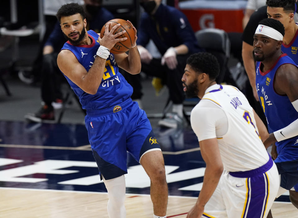 Denver Nuggets guard Jamal Murray, left, pulls in a rebound as Los Angeles Lakers forward Anthony Davis defends in the first half of an NBA basketball game Sunday, Feb. 14, 2021, in Denver. (AP Photo/David Zalubowski)