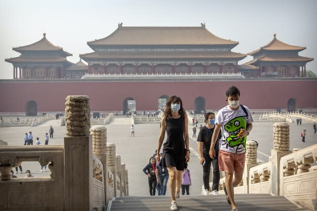 Visitors wearing face masks walk through the Forbidden City in Beijing, China (AP/Mark Schiefelbein)