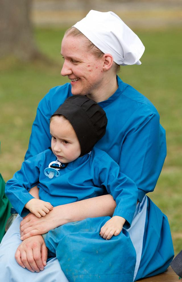 Anna Miller holds her daughter during a farewell picnic outside the school house in Bergholz, Ohio on Tuesday, April 9, 2013. The farewell celebration was held for Miller and other Amish members leaving for prison throughout the week for their roles in a hair and beard cutting scandal. (AP Photo/Scott R. Galvin)