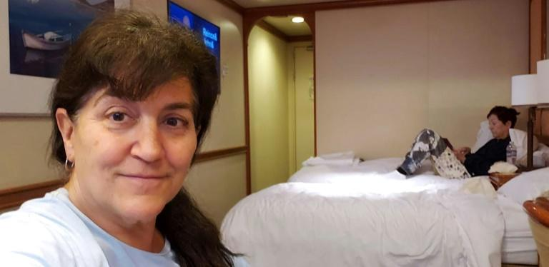 This handout photo released by Carolyn Wright, a passenger on the Grand Princess cruise ship, shows her taking a selfie alongside her friend Beryl Ward in their cabin on the ship on March 7, 2020