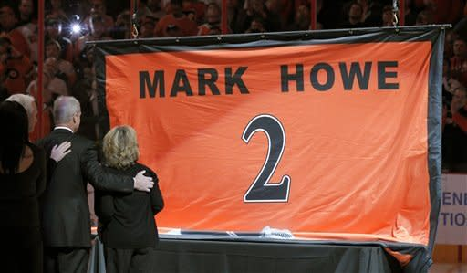 Gordie Howe, left, Mark Howe, second from right, and Ginger Howe, right, watch as NHL Hall of Famer Mark Howe's jersey number is raised during a ceremony to retire the number, before an NHL hockey game between the Philadelphia Flyers and the Detroit Red Wings on Tuesday, March 6, 2012, in Philadelphia. (AP Photo/Alex Brandon)