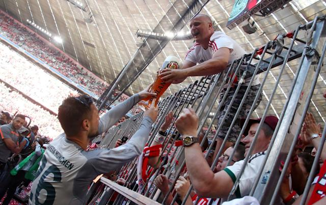 Soccer Football - Bundesliga - Bayern Munich v VfB Stuttgart - Allianz Arena, Munich, Germany - May 12, 2018 Bayern Munich's Sven Ulreich holds a glass of beer with a fan as they celebrate winning the Bundesliga REUTERS/Michael Dalder DFL RULES TO LIMIT THE ONLINE USAGE DURING MATCH TIME TO 15 PICTURES PER GAME. IMAGE SEQUENCES TO SIMULATE VIDEO IS NOT ALLOWED AT ANY TIME. FOR FURTHER QUERIES PLEASE CONTACT DFL DIRECTLY AT + 49 69 650050
