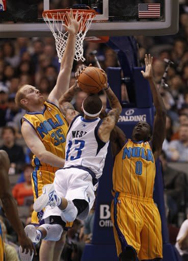 Dallas Mavericks guard Delonte West (13) shoots against New Orleans Hornets defenders Chris Kaman (35) and Al-Farouq Aminu (0) during the first half of an NBA basketball game in Dallas on Saturday, Jan. 7, 2012. (AP Photo/Mike Fuentes)