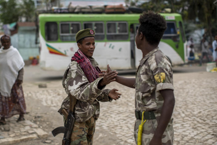 FILE - In this Friday, May 7, 2021 file photo, fighters loyal to the Tigray People's Liberation Front (TPLF) greet each other on the street in the town of Hawzen, then-controlled by the group but later re-taken by government forces, in the Tigray region of northern Ethiopia. The Tigray forces that in late June 2021 have retaken key areas after fierce fighting have rejected the cease-fire and vowed to chase out Ethiopian government forces and those of neighboring Eritrea. (AP Photo/Ben Curtis, File)