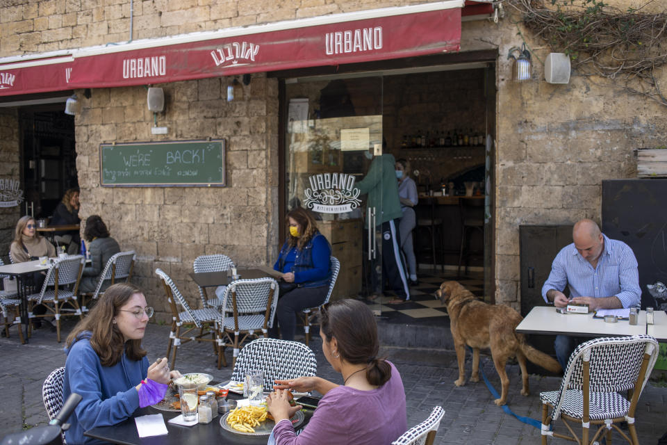 People eat in a restaurant as restrictions are eased following months of government-imposed shutdowns, in Tel Aviv, Israel on March 7, 2021. (Ariel Schalit/AP)