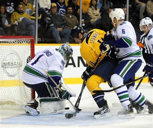 Vancouver Canucks goalie Roberto Luongo (1) stops a shot by Nashville Predators center David Legwand (11) as he is checked by Canucks defenseman Sami Salo (6), of Finland, in the second period of an NHL hockey game on Tuesday, Feb. 7, 2012, in Nashville, Tenn. (AP Photo/Mike Strasinger)