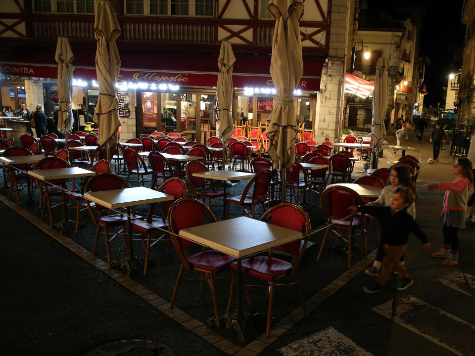 Children walk by a restaurant as it closes a few minutes before curfew in Saint Jean de Luz, southwestern France, Saturday, Oct. 24, 2020. A curfew intended to curb the spiraling spread of the coronavirus, has been imposed in many regions of France including Paris and its suburbs. (AP Photo/Bob Edme)