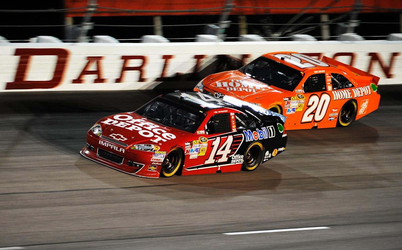 DARLINGTON, SC - MAY 12:  Tony Stewart, driver of the #14 Office Depot/Mobil 1 Chevrolet, leads Joey Logano, driver of the #20 The Home Depot Toyota, during the NASCAR Sprint Cup Series Bojangles' Southern 500 at Darlington Raceway on May 12, 2012 in Darlington, South Carolina.  (Photo by Rainier Ehrhardt/Getty Images for NASCAR)