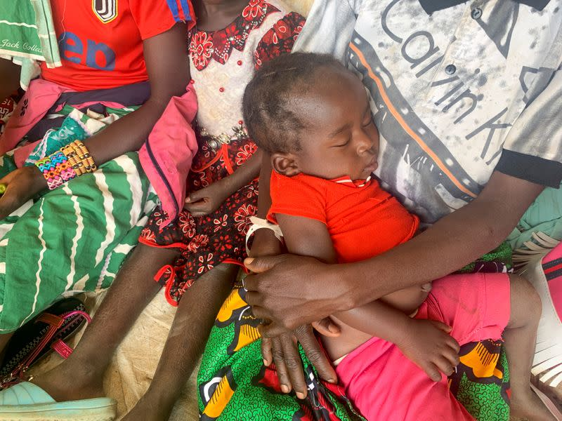 A woman who fled the violent rebellion in Central African Republic (CAR) holds her sleeping child as they wait for their identification process in the border town of Garoua Boulai