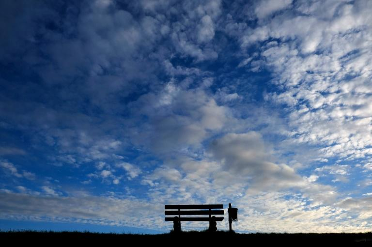 An empty bench silhouettes against the evening sky in Emden, northern Germany, as many activities slowed down or came to a halt to fight the spread of the novel coronavirus