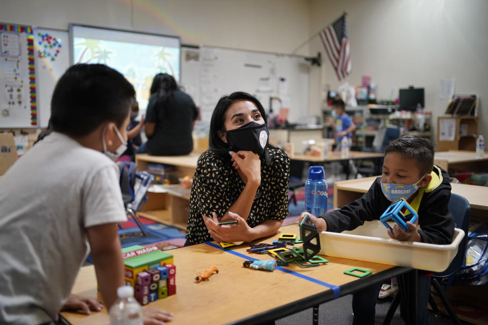 Teacher Juliana Urtubey, center, works with Brian Avilas, left, and Jesus Calderon Lopez, right, in a class at Kermit R Booker Sr Elementary School Wednesday, May 5, 2021, in Las Vegas. Urtubey is the the 2021 National Teacher of the Year. (AP Photo/John Locher)