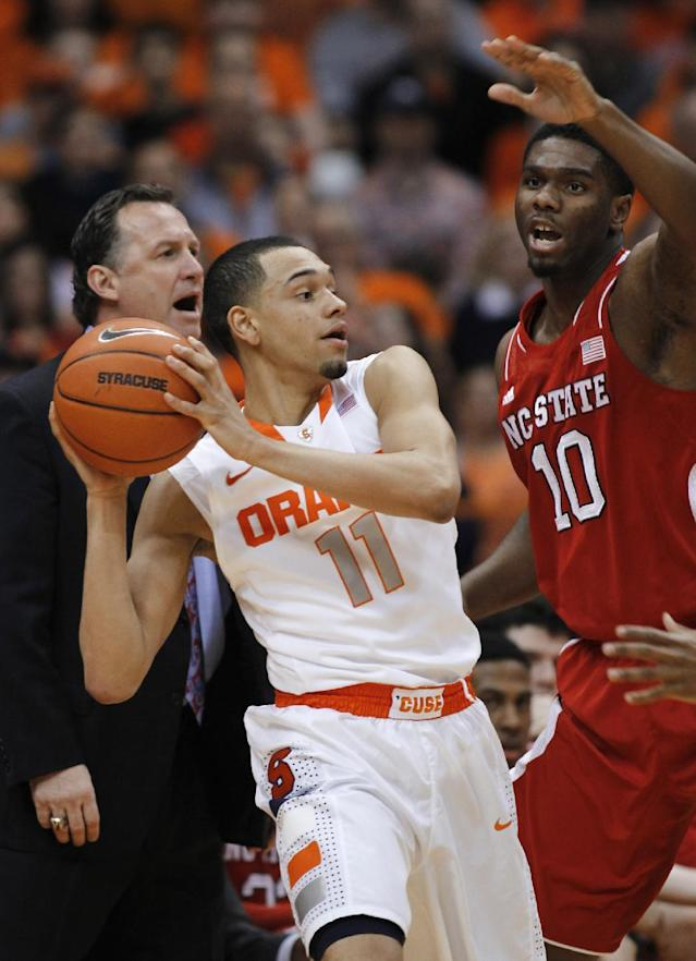 Syracuse Tyler Ennis, left, looks to pass the ball against North Carolina State's Lennard Freeman, right, during the first half of an NCAA college basketball game in Syracuse, N.Y., Saturday, Feb. 15, 2014. North Carolina State's head coach Mark Gottfried, back, calls out to his players. (AP Photo/Nick Lisi)