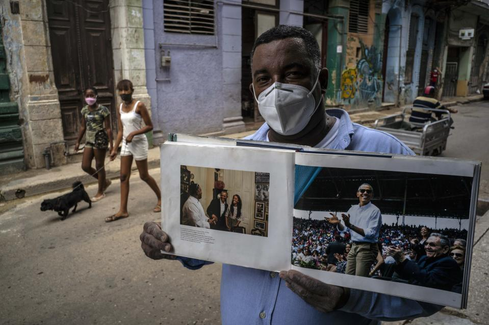 "Wearing a face mask amid the new coronavirus pandemic, Cristobal Marquez, owner of ""Cristobal's,"" the restaurant where Michelle and Barak Obama had lunch during their visit to Cuba in 2016, shows the book made by White House photographer Pete Souza, in Havana, Cuba, Thursday, Oct. 22, 2020. Obama restored diplomatic relations, loosened restrictions on travel and remittances and became the first U.S. chief of state to set foot in the island in 88 years. (AP Photo/Ramon Espinosa)"
