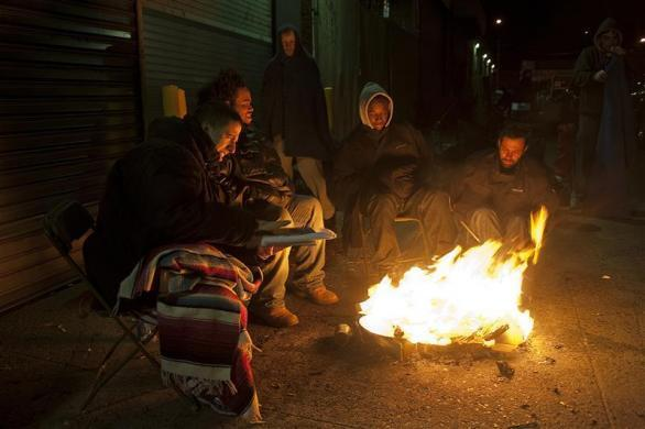 Job seekers congratulate themselves around a fire after getting their job applications in front of the training offices of Local Union 46, the union representing metallic lathers and reinforcing ironworkers, in Queens borough of New York, April 30, 2012.