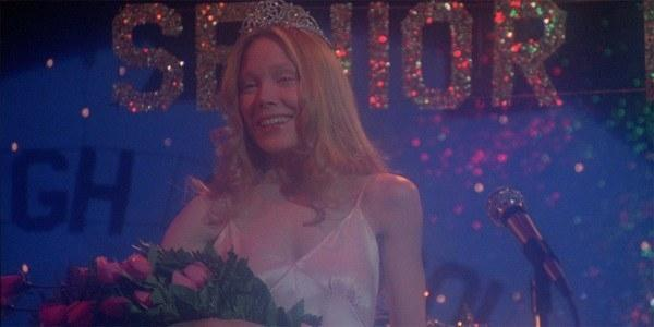 Carrie standing on stage with the homecoming crown on her head during the senior prom