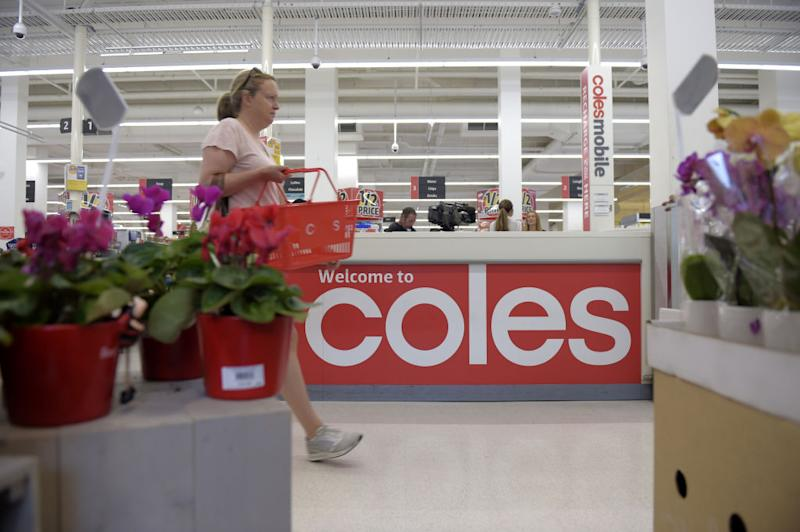 Pictured: Shopper walks with grocery basket in Coles supermarket. Image: Getty