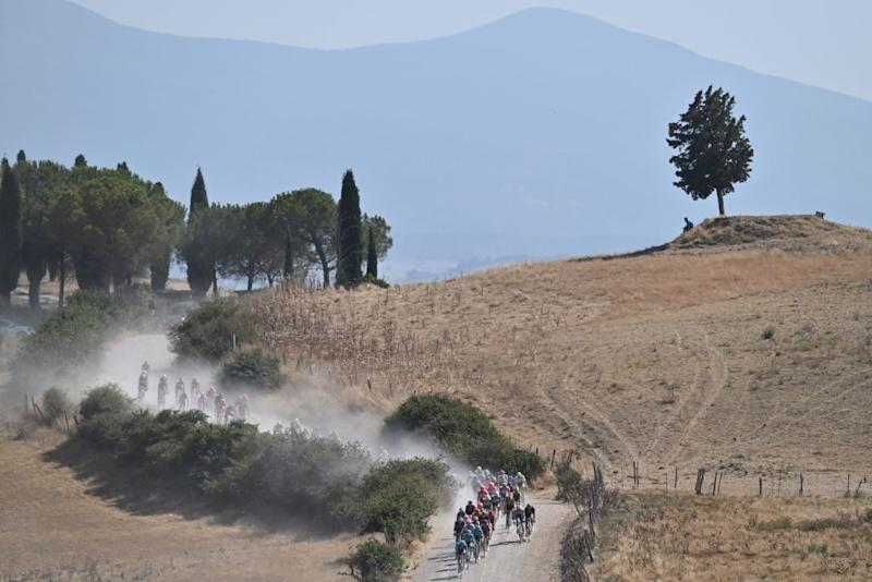 The pack of riders pedal through a dusty gravel road during the oneday classic cycling race Strade Bianche White Roads on August 1 2020 around Siena Tuscany Photo by Marco BERTORELLO AFP Photo by MARCO BERTORELLOAFP via Getty Images