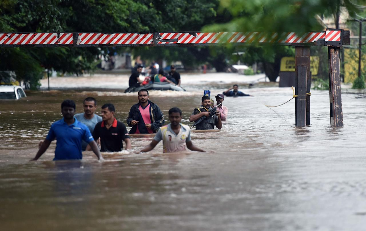 SANGLI, INDIA - AUGUST 9: People walk through flooded Streets of Sangli, on August 9, 2019 in Sangli, India. Teams of the National Disaster Response Force, Indian Army and Navy continued evacuating people to safer locations in boats in coordination with the local administration. Despite decrease in the intensity of rainfall, the flood situation in Sangli and Kolhapur continues to be serious with the death toll rising to 27, including nine persons who died as the private rescue boat carrying them overturned in Bramhnal village in Palus taluka of Sangli district. (Photo by Pratham Gokhale/Hindustan Times via Getty Images)
