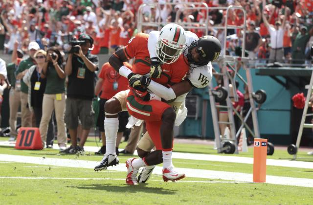 Wake Forest's Kevin Johnson, right, tries to tackle Miami's Herb Waters (6) after he scored a touchdown during the first half of an NCAA college football game in Miami Gardens, Fla., Saturday, Oct. 26, 2013. (AP Photo/J Pat Carter)