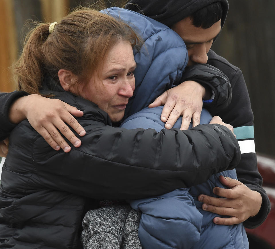 Family members mourn at the scene where their loved ones were killed early Sunday, May 9, 2021, in Colorado Springs, Colo. The suspected shooter was the boyfriend of a female victim at the party attended by friends, family and children. He walked inside and opened fire before shooting himself, police said. Children at the attack weren't hurt and were placed with relatives. (Jerilee Bennett/The Gazette via AP)