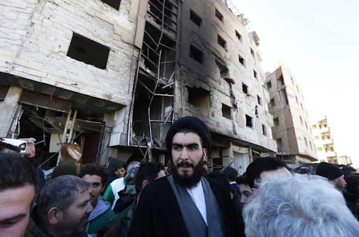 A Shiite cleric stands amid Syrian pro-government forces and residents at the site of suicide bombings in the area of a revered Shiite shrine in the town of Sayyida Zeinab, on the outskirts of the capital Damascus, on January 31, 2016 (AFP Photo/Louai Beshara)