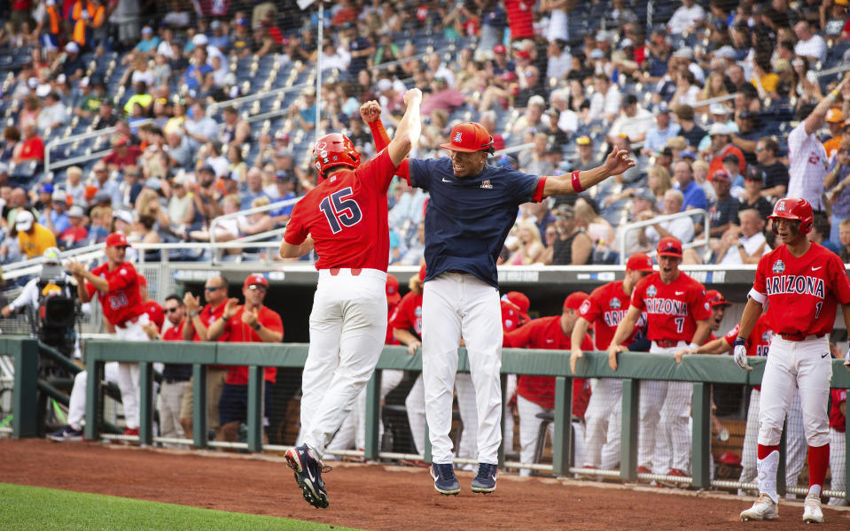 Arizona's Jacob Berry (15), left, celebrates with teammate Chase Davis (8) after scoring off a hit by Branden Boissiere (not shown) against Vanderbilt in the first inning during a baseball game in the College World Series, Saturday, June 19, 2021, at TD Ameritrade Park in Omaha, Neb. (AP Photo/Rebecca S. Gratz)