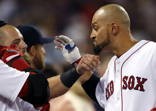 Boston Red Sox's Shane Victorino has his beard pulled by teammate Mike Napoli as he celebrates at the dugout after hitting a three-run homer against the Baltimore Orioles in the fifth inning of a baseball game at Fenway Park in Boston, Tuesday, Aug. 27, 2013. (AP Photo/Elise Amendola)