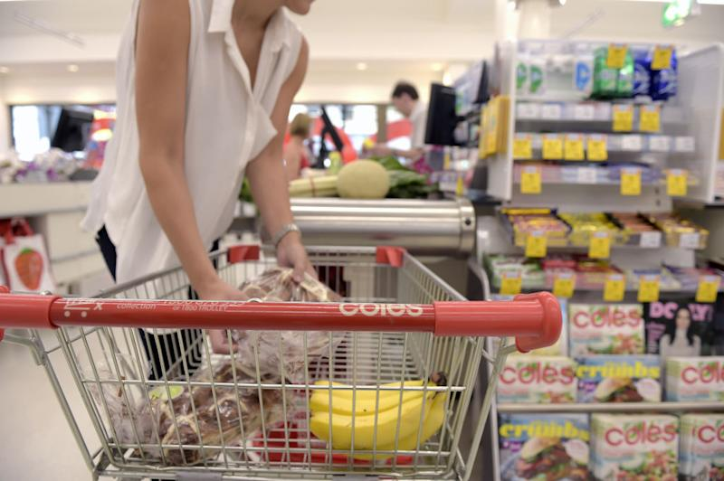 A customer moves items from a shopping cart to a checkout counter at a Coles supermarket.