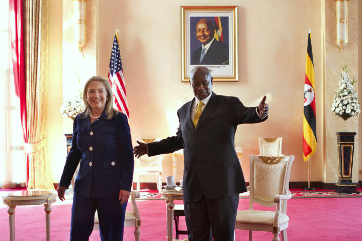 """FILE - In this Friday, Aug. 3, 2012 file photo, Secretary of State Hillary Rodham Clinton, left, meets with Ugandan President Yoweri Museveni, right, at the State House in Kampala, Uganda. Ugandan President Yoweri Museveni met in his office with a team of U.S.-based rights activists concerned about legislation that would impose life sentences for some homosexual acts and made clear he had no plans to sign the bill, according to Santiago Canton of the Robert F. Kennedy Center for Justice and Human Rights who attended the Jan. 18, 2014 meeting, but one month later Museveni appears to have changed his mind, saying through a spokesman in February 2014 that he would sign the bill """"to protect Ugandans from social deviants."""" (AP Photo/Jacquelyn Martin, Pool, File)"""