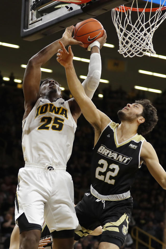 Iowa forward Tyler Cook (25) is fouled by Bryant guard Joe Kasperzyk (22) while driving to the basket during the second half of an NCAA college basketball game, Saturday, Dec. 29, 2018, in Iowa City, Iowa. (AP Photo/Charlie Neibergall)